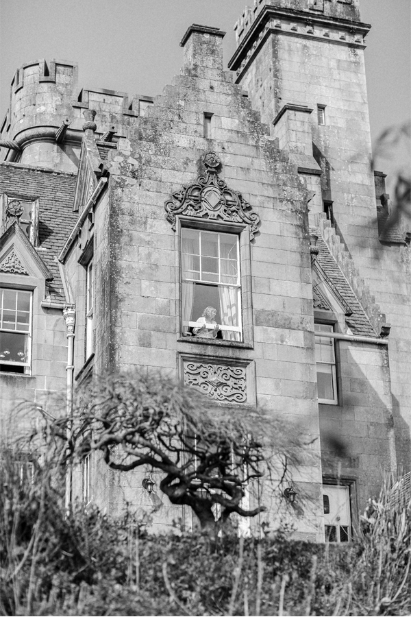 bride opening a window at stonefield castle scotland