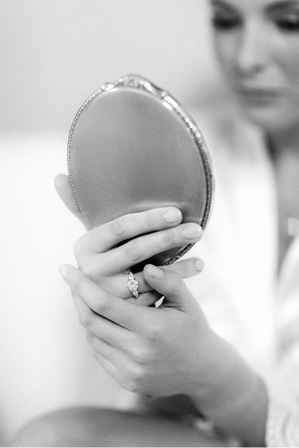 bride looking at a mirror with engagagment ring