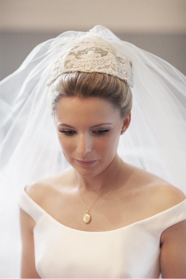 bride looking down having her veil fixed