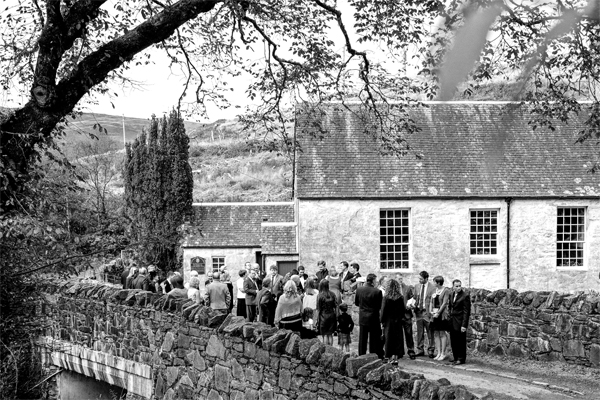 wedding guests gathers in front of a scottish church