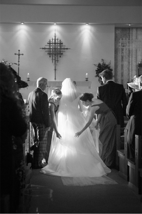 bride having her dress and veil fixed at church ceremony