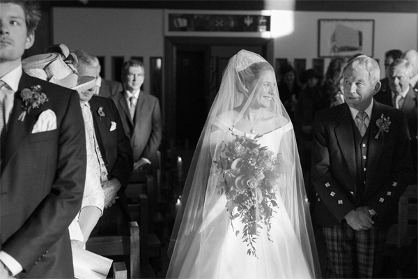 bride smiling to her father while walking down the aisle