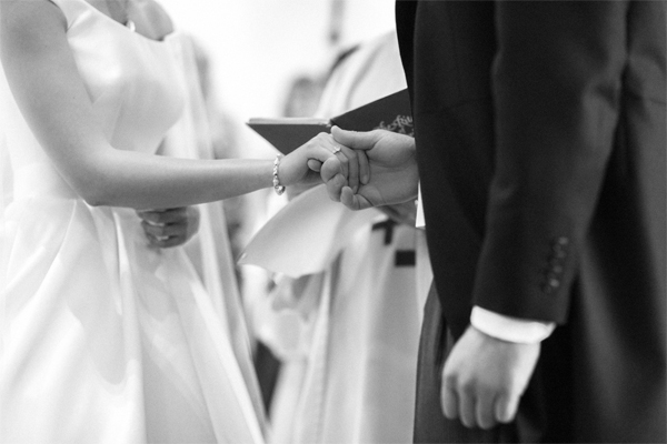 bride and groom holding their hands during roman catholic ceremony