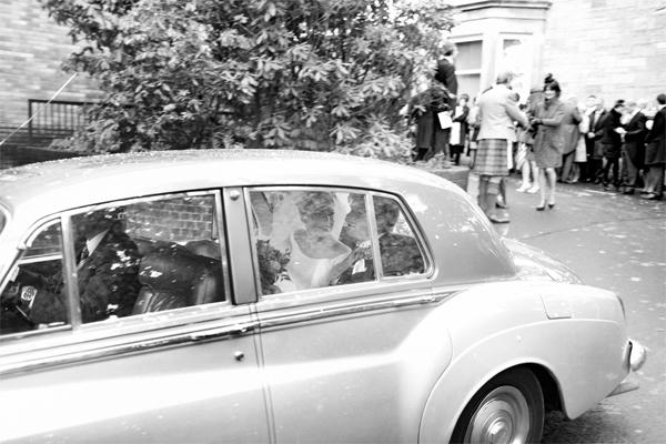 newlyweds leaving teh church in a wedding car