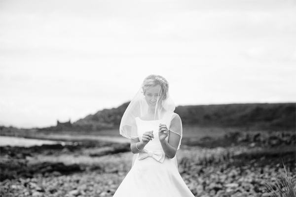 bride playing with his veil on a beach