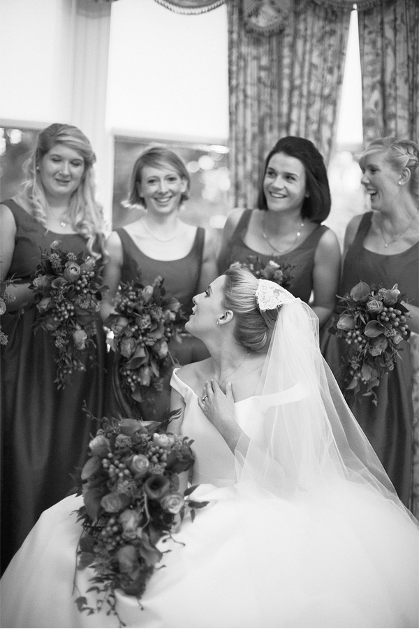 bride and bridesmates laughing during wedding photo session