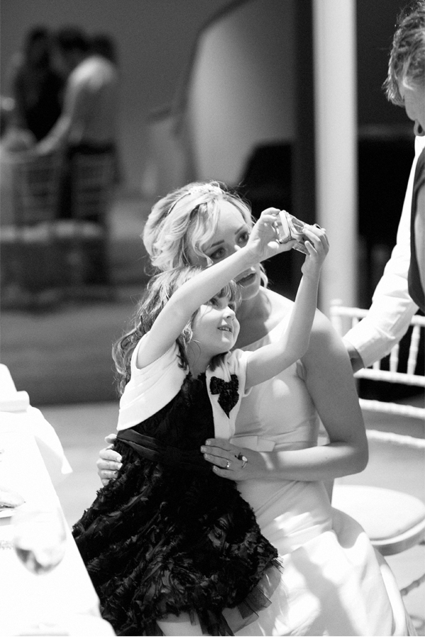 little girl take photo with bride