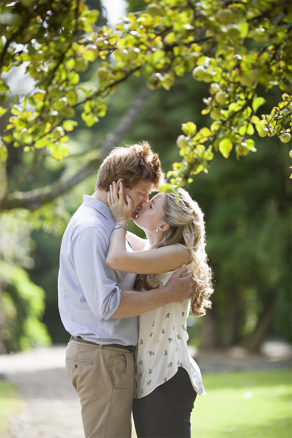 engaged couple kissing under an apple tree garden glasgow