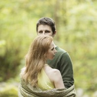 engaged couple in a forest in scotland holding each other with shawl