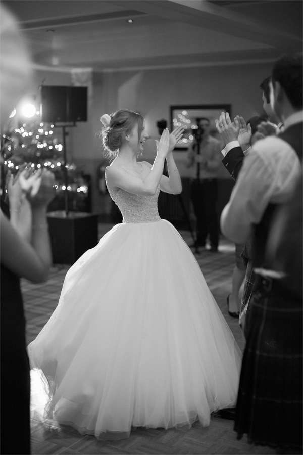 bride laughing and claping after first dance