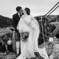 married couple kissing in an old harbour scotland isle of harris