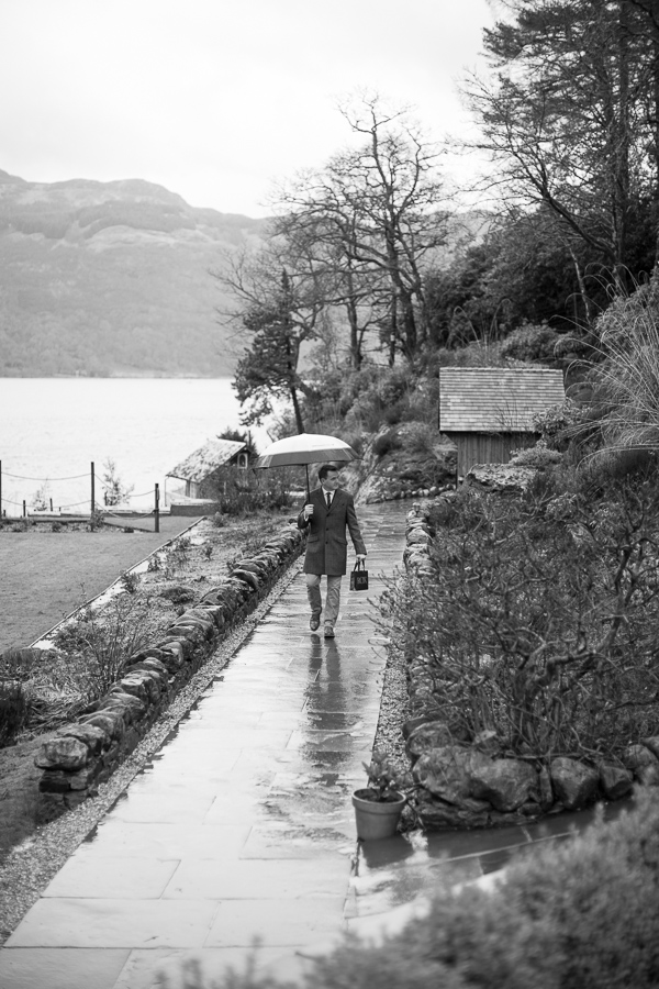 groom walking in the rain for ceremony at the lodge on loch goil scotland