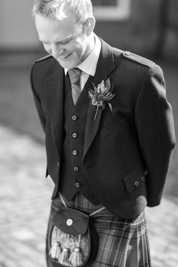 groom looking down dressed in scottish kilt