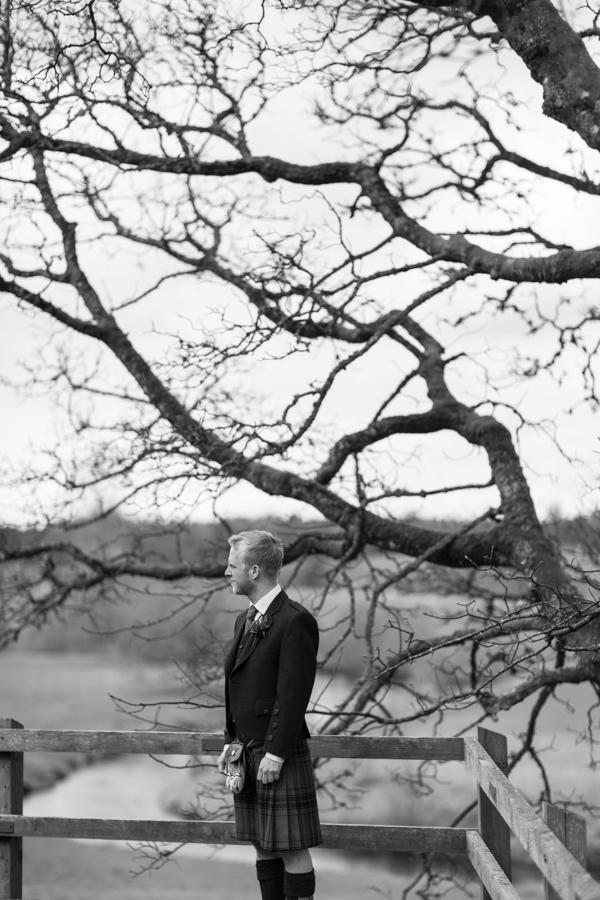 groom standing next to big tree