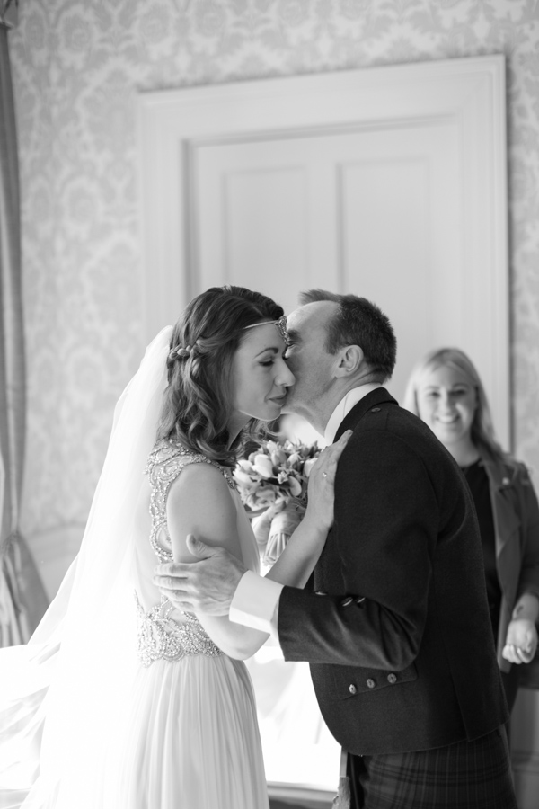 father kissing the bride after seeing her in the wedding dress
