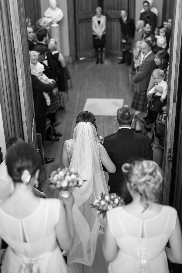bride walking down with father and bridesmates for ceremony