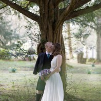 couple kissing during wedding under tree at blairquhan castle wedding photographer ayrshire