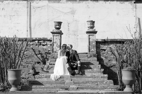 bride and groom sitting and kissing at a garden