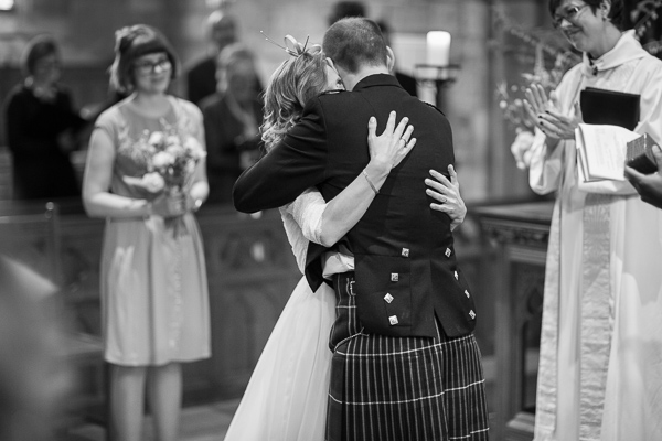 bride and groom embraced during church wedding ceremony