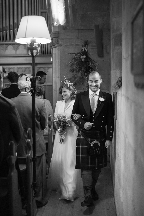 newlyweds walk out of the church near edinburgh