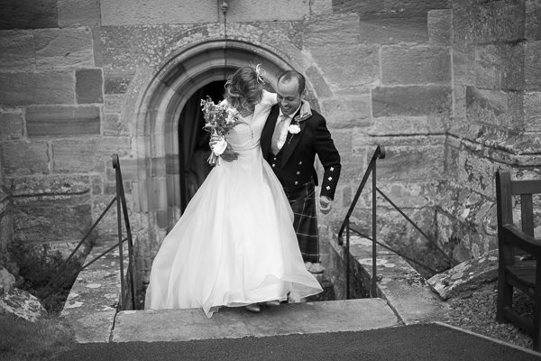 groom lifts the bride on the steps from the church fotogenic of scotland