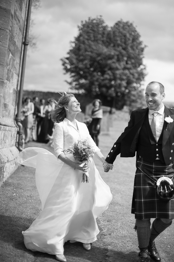 bride and groom very excited just married outside the church in scotland