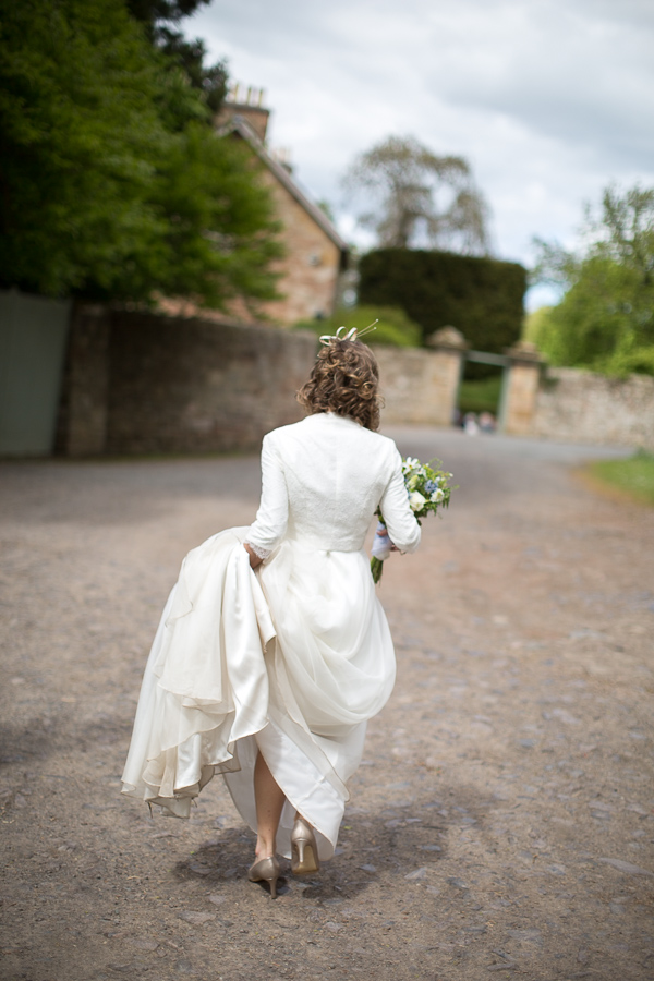 bride walking alone holding her dress