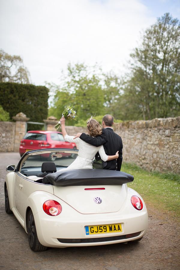 newlyweds driving away in a VW beattle in edinburgh scotland