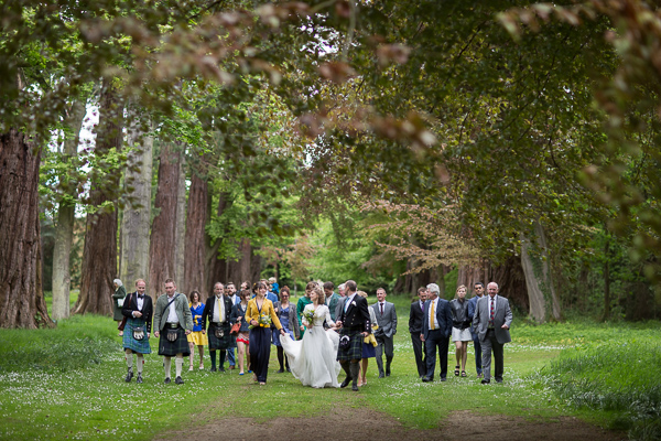 bride and groom leading the procession of guests to wedding venue near edinburgh