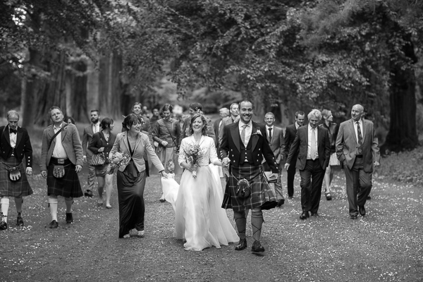 wedding party walking through the forest at oxenford castle in scotland