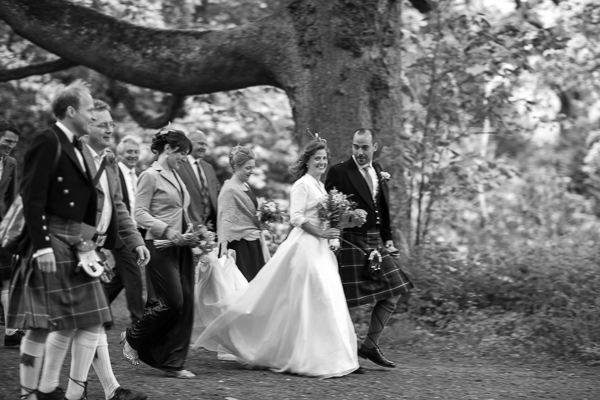bride and groom walking with thier guests to ther wedding venue