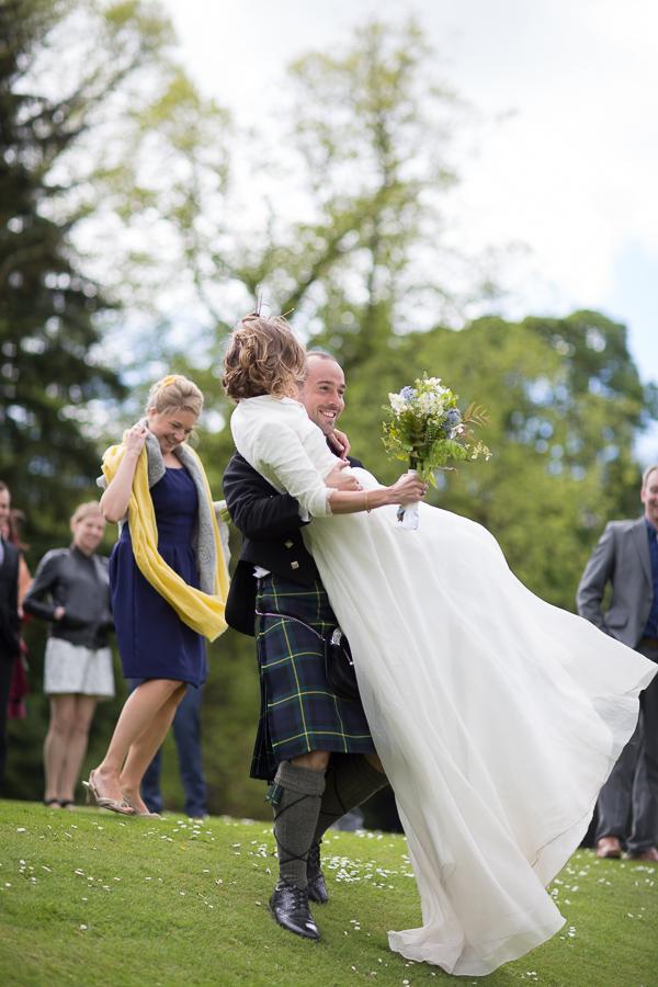 wedding photographer edinburgh scotland groom lifting bride