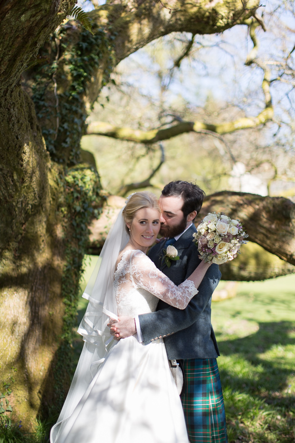 newlyweds embraced under a large tree at boturich castle gardens