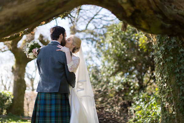 just married kissing under a large tree loch lomond wedding photographer