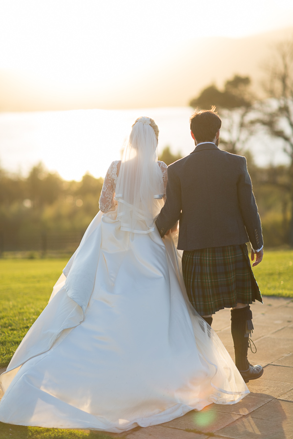 newlyweds walking away towards loch lomond and sunset