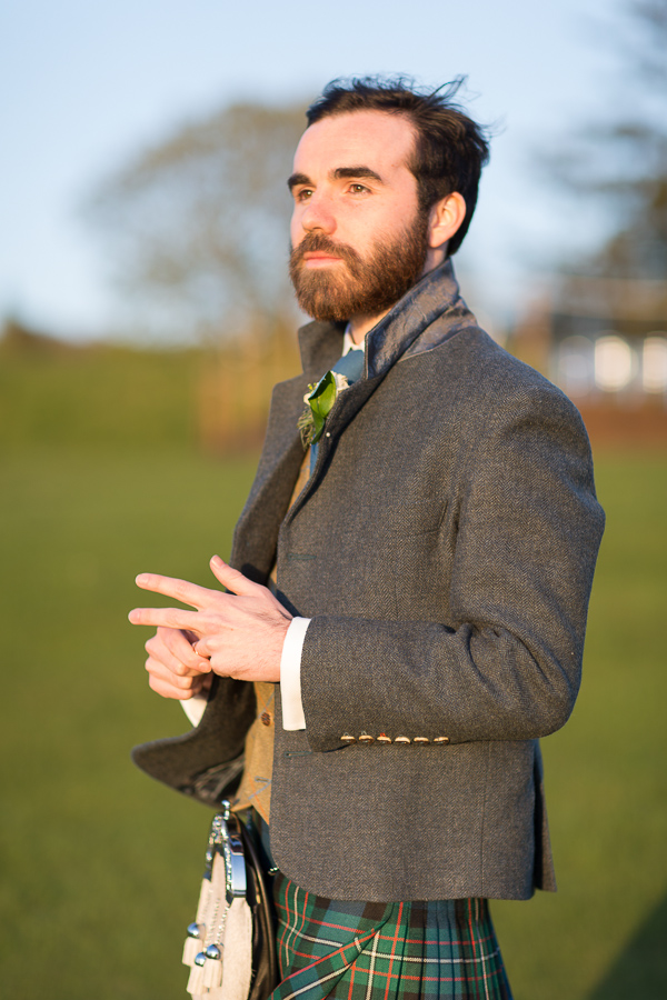 groom holding his ring on a finger looking away