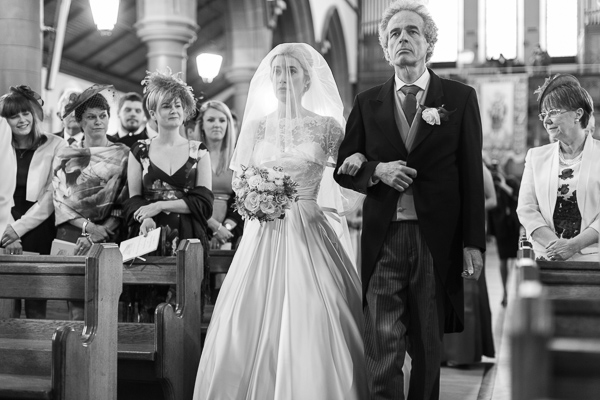 bride walking down at a large church ceremony