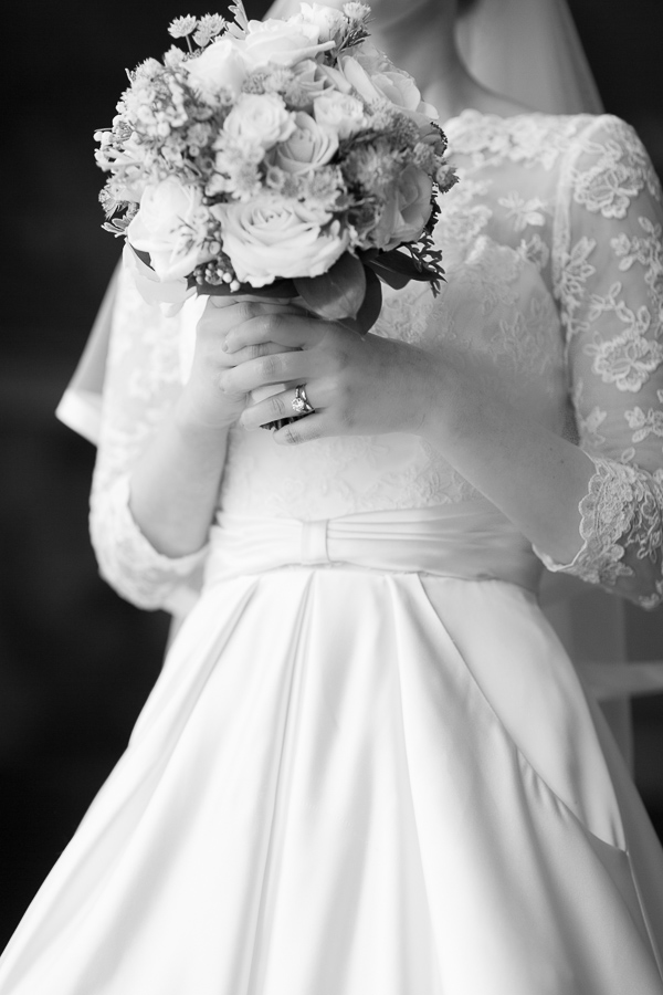 bride holding flowers, wedding ring visible