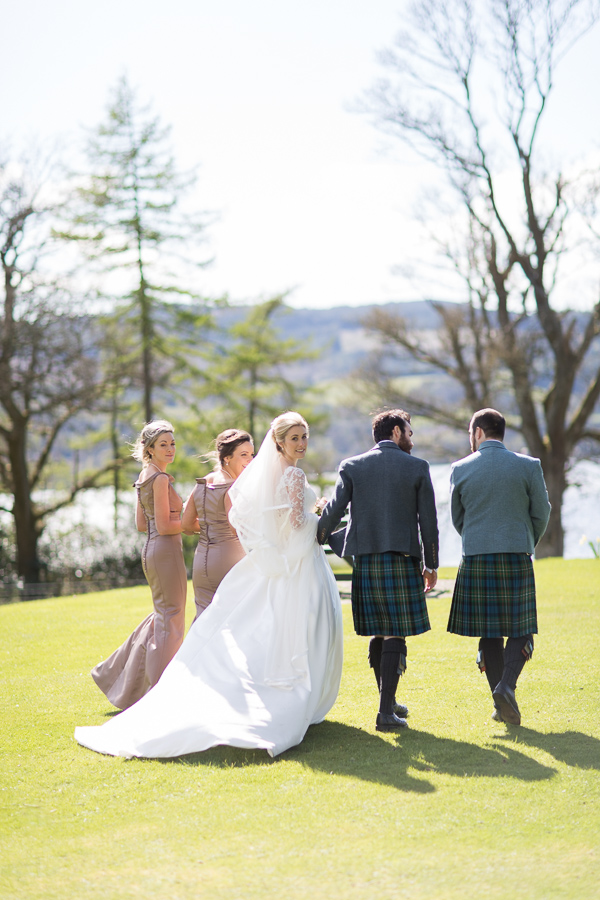 bridal party walking away with loch lomond in the distance