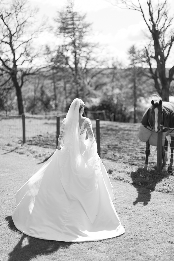 bride walking closer to a horse at boturich castle on loch lomond wedding