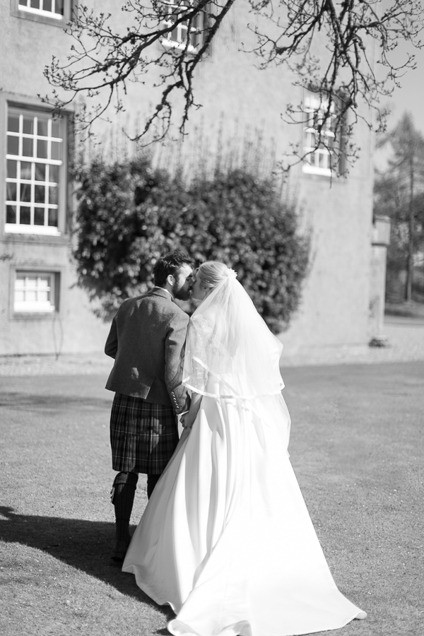 newlyweds kissing while walkng away towards boturich castle