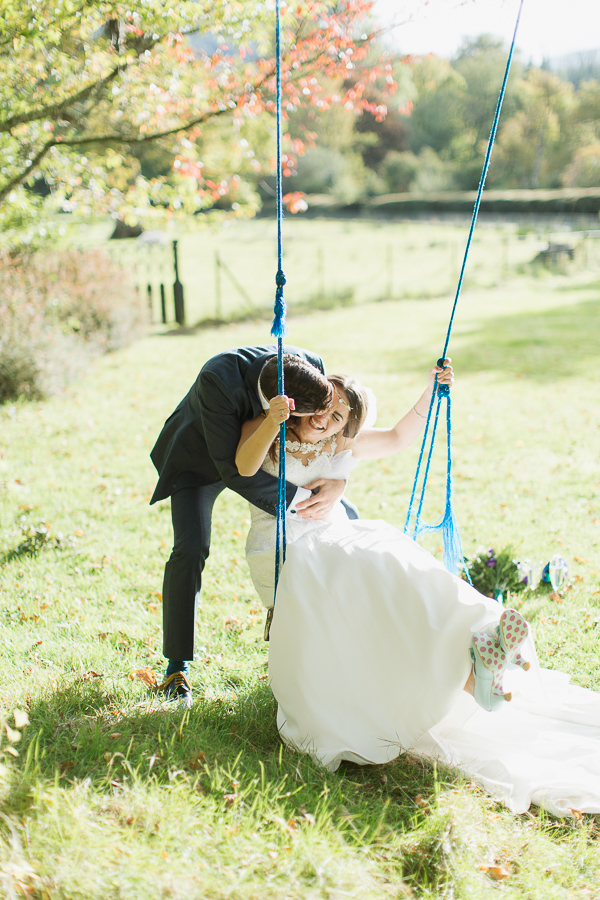 bride and groom embraced kissing on swing near glasgow