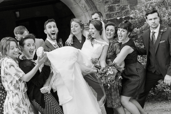 bride beeing lifted by groom and friends