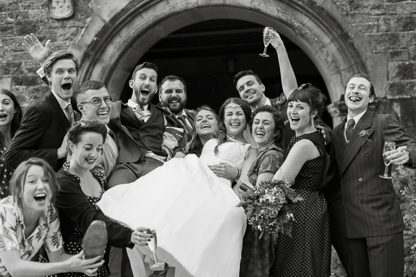 friends going crazy at wedding lifting bride and groom