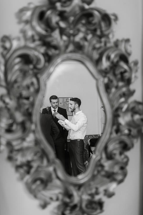 mirro relfection of groom talking to groomsmen scotland