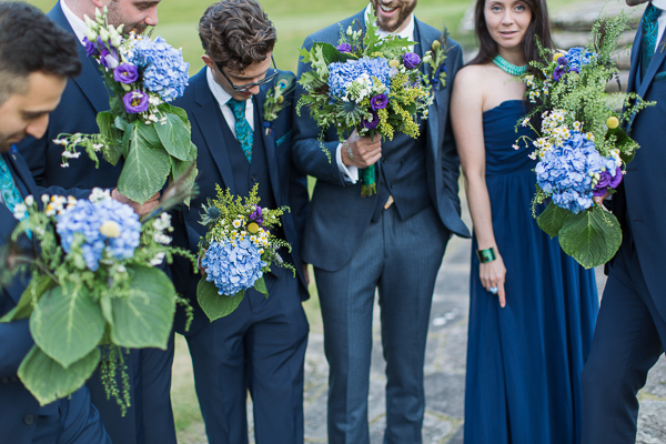 groom and grooms party holding flowers