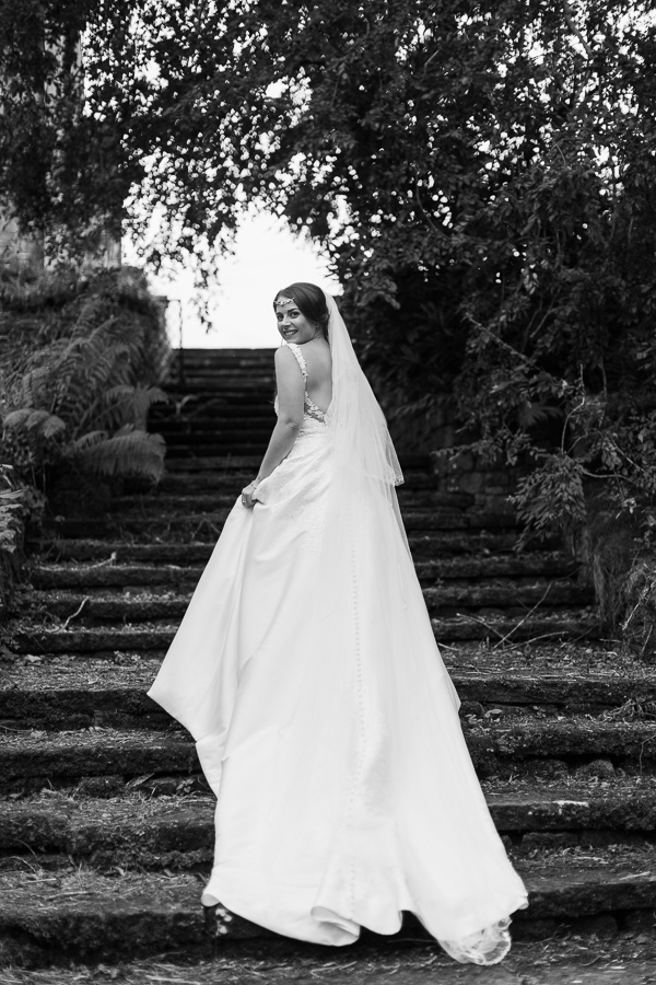 bride standing on stairs with long wedding dress