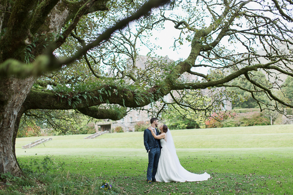 bride and groom under large tree in ardkinglas garden photo by fotogenic of scotland
