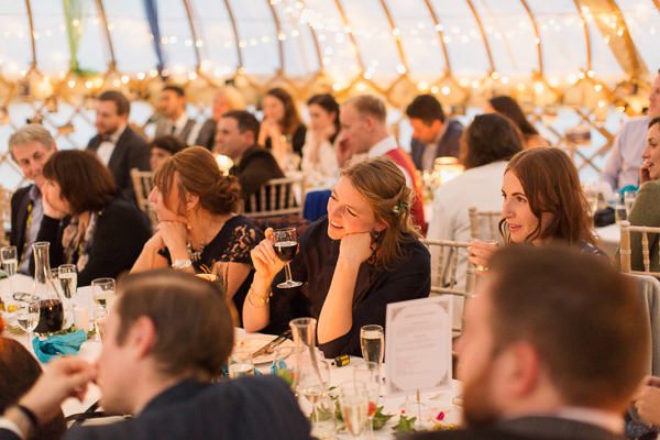 wedding guests during speeches in tipi tent