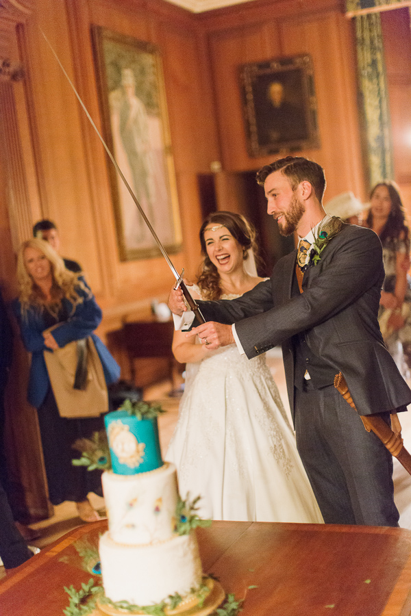 bride and groom preparing for cutting of the cake with sword in scotland